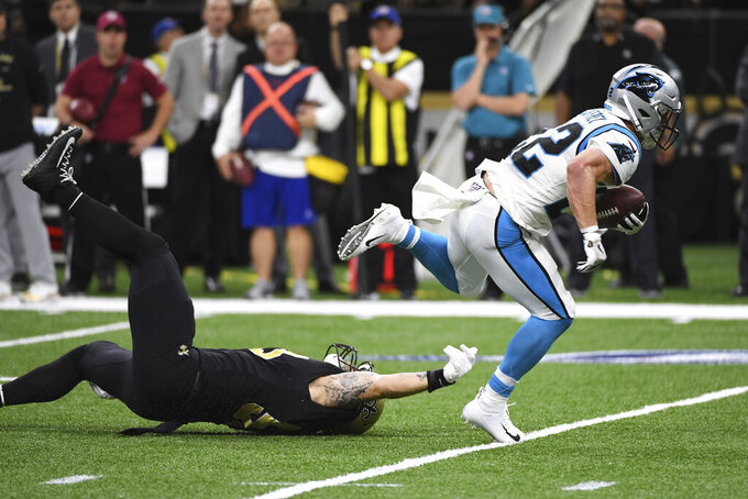 New Orleans Saints outside linebacker Demario Davis (56) can't hold onto Carolina Panthers running back Christian McCaffrey (22), during the first half at an NFL football game, Sunday, Nov. 24, 2019, in New Orleans. (AP Photo/Bill Feig)
