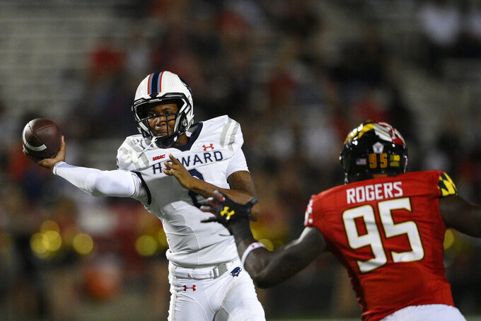 Howard quarterback Quinton Williams, left, passes under pressure from Maryland defensive lineman Lawtez Rogers (95) during the first half of an NCAA college football game, Saturday, Sept. 11, 2021, in College Park, Md. (AP Photo/Nick Wass)