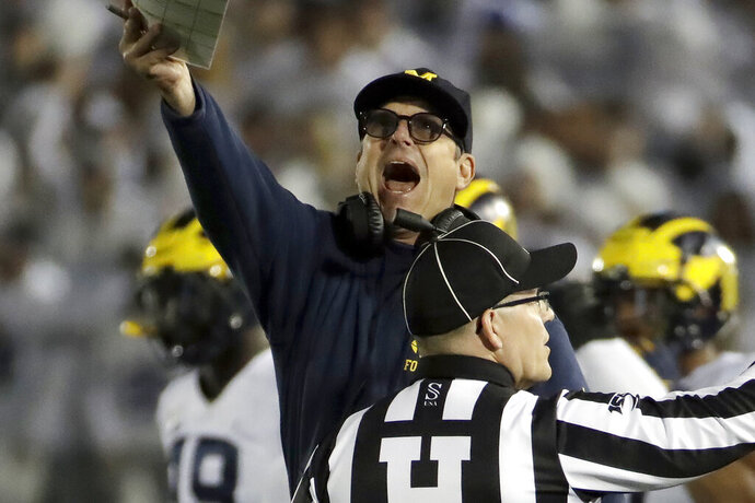 Michigan coach Jim Harbaugh, center, argues a call during the first half of the team's NCAA college football game against Penn State in State College, Pa., Saturday, Oct. 19, 2019. (AP Photo/Gene J. Puskar)