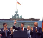 FILE - In this on Friday, June 12, 1987 file photo, U.S. President Ronald Reagan acknowledges the applause after speaking to an audience in front of the Brandenburg Gate in Berlin. Beside Reagan are the President of the German Parliament Philipp Jenninger, left, and Germany's Chancellor Helmut Kohl, right. The U.S. Embassy in Berlin is unveiling the statue of Ronald Reagan as a tribute to the 30th anniversary of the fall of the Berlin Wall. The larger-than-life statue is being installed Friday atop the embassy's terrace, at eye-level with the landmark Brandenburg Gate in downtown Berlin. (AP PHOTO/Ira Schwartz, File)