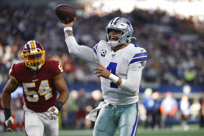 FILE - In this Dec. 15, 2019, file photo, Dallas Cowboys quarterback Dak Prescott (4) delivers a touchdown pass to running back Ezekiel Elliott during the first half of an NFL football game against the Washington Redskins in Arlington, Texas. The two biggest losses in free agency for the Dallas Cowboys were at cornerback and defensive end, so it's reasonable to list those as the club's top two priorities going into the draft. (AP Photo/Ron Jenkins, File)