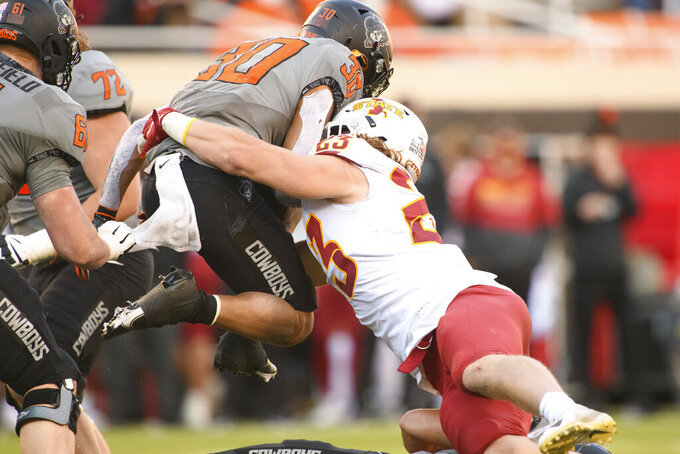 Iowa State linebacker Mike Rose (23) grabs a leaping Oklahoma State running back Chuba Hubbard (30) out of the air during an NCAA college football game Saturday, Oct. 24, 2020, in Stillwater, Okla. Oklahoma State defeated Iowa State 24-21. (AP Photo/Brody Schmidt)