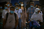 People wearing face masks to protect against the coronavirus wait to cross an intersection in the central business district in Beijing, Wednesday, July 15, 2020. China is further easing restrictions on domestic tourism after reporting no new local cases of COVID-19 in nine days. (AP Photo/Mark Schiefelbein)
