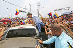 National Assembly President and self-proclaimed interim president of Venezuela, Juan Guaido, climbs on the top of a vehicle to greet supporters during a rally on the shores of Maracaibo Lake in Cabimas, Venezuela, Sunday, April 14, 2019. The international coalition that supports the opposition stands at 54 nations, although some longtime U.S. allies have refused to join the Trump administration in recognizing the head of the National Assembly, Juan Guaido, as interim president. (AP Photo/Fernando Llano)