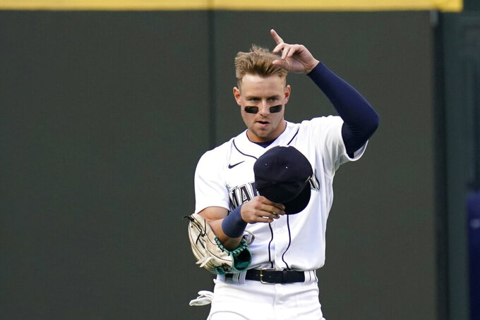 Seattle Mariners left fielder Jarred Kelenic acknowledges fans as he takes his place on the field in the first inning of a baseball game Thursday, May 13, 2021, in Seattle. The game was Kelenic's major league debut. (AP Photo/Elaine Thompson)