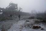 In this photo taken on Tuesday, Nov. 19, 2019, a Ukrainian soldier passes by a destroyed Butovka coal mine as he approaches his front line position in the town of Avdiivka in the Donetsk region, Ukraine. U.S.-made X-ray equipment, helmets and missiles make a difference for Ukrainian troops fighting Kremlin-backed separatists on the front line of the 21st century standoff between Russia and the West. (AP Photo/Vitali Komar)