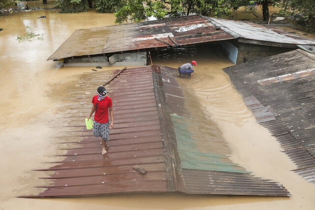 A man walks on top of a roof of a submerged house as floods inundate villages due to Typhoon Vamco in Rizal province, Philippines on Thursday Nov. 12, 2020. The typhoon swelled rivers and flooded low-lying areas as it passed over the storm-battered northeast Philippines, where rescuers were deployed early Thursday to help people flee the rising waters. (AP Photo/Basilio Sepe)