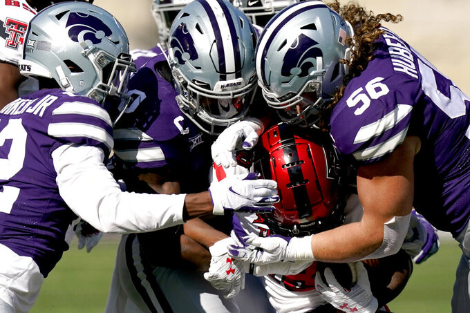 Texas Tech wide receiver Myles Price, center, is tackled by Kansas State defensive back AJ Parker, left, and defensive end Wyatt Hubert (56) during the first half of an NCAA college football game Saturday, Oct. 3, 2020, in Manhattan, Kan. (AP Photo/Charlie Riedel)