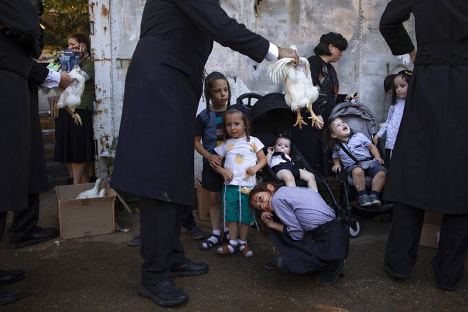 An Ultra-Orthodox Jewish man swings a chicken over his kids as part of the Kaparot ritual in Bnei Brak, Israel, Tuesday, Sept. 14, 2021. Observant Jews believe the ritual transfers one's sins from the past year into the chicken, and is performed before the Day of Atonement, Yom Kippur, the holiest day in the Jewish year which starts at sundown Wednesday. (AP Photo/Oded Balilty)