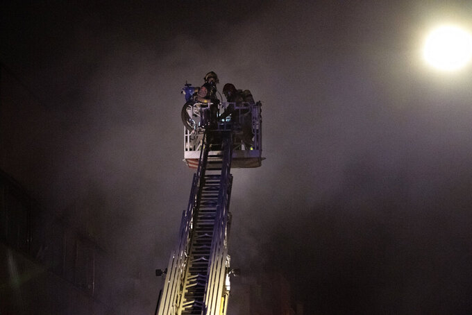 Firefighters work to extinguish a fire at a building in Badalona, Barcelona, Spain, Thursday, Dec. 10, 2020. Authorities in northeastern Spain say a fire has raged through an abandoned building occupied by squatters in the city of Badalona, injuring at least 17 people, including two in critical condition. Firefighters say they rescued around 30 people from windows as the building burned late Wednesday. (AP Photo/Joan Mateu)