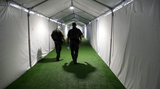 FILE - In this May 2, 2019, file photo, U.S. Border Patrol agents walk down the hallway of a new U.S. Customs and Border Protection temporary facility near the Donna International Bridge in Donna, Texas. The U.S. government says it will deport a Honduran mother and her two sick children, both of whom are currently hospitalized, to Guatemala as soon as it can get them medically cleared to travel, according to court documents and the family's advocates. (AP Photo/Eric Gay, File)