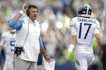 Tennessee Titans head coach Mike Vrabel, left, talks with quarterback Ryan Tannehill during the second half of an NFL football game against the Seattle Seahawks, Sunday, Sept. 19, 2021, in Seattle. The Titans won 33-30 in overtime. (AP Photo/John Froschauer)