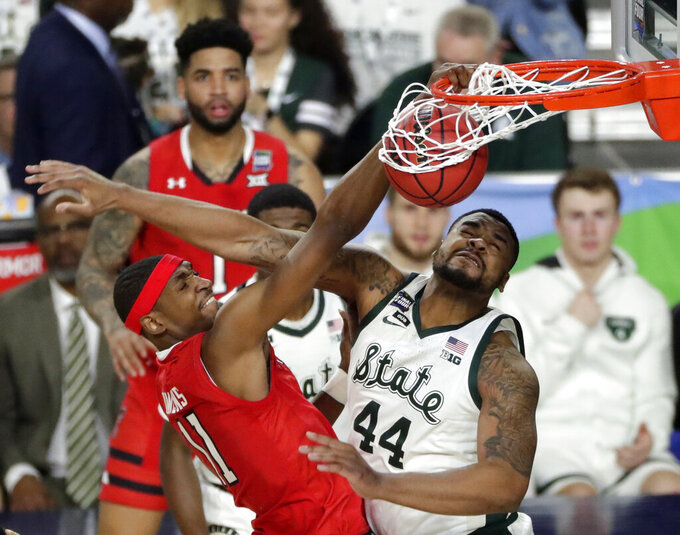 Texas Tech forward Tariq Owens, left, dunks the ball over Michigan State forward Nick Ward (44) during the first half in the semifinals of the Final Four NCAA college basketball tournament, Saturday, April 6, 2019, in Minneapolis. (AP Photo/Matt York)