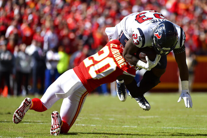 Kansas City Chiefs cornerback Morris Claiborne (20) tackles Houston Texans running back Carlos Hyde (23) during the first half of an NFL football game in Kansas City, Mo., Sunday, Oct. 13, 2019. (AP Photo/Ed Zurga)