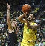 Oregon's Ehab Amin, right, passes the ball under pressure from Oregon State's Zach Reichle, left, during the first half of an NCAA college basketball game Saturday, Jan. 5, 2019, in Eugene, Ore. (AP photo/Chris Pietsch)