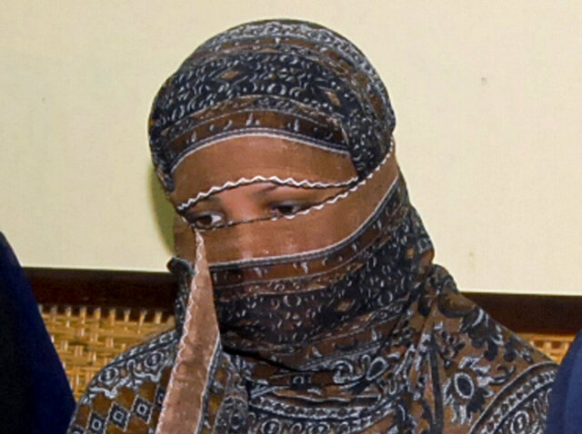 FILE - In this Nov. 20, 2010, file photo, Asia Bibi, a Pakistani Christian woman, listens to officials at a prison in Sheikhupura near Lahore, Pakistan. Asia Bibi will receive Tuesday her diploma as a Citizen of Honor of the city of Paris, a title she was awarded in 2015. She is to meet French President Emmanuel Macron on Friday, the Elysee said. (AP Photo, File)
