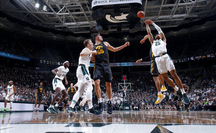 Michigan State's Malik Hall, right and Iowa's Luka Garza (55) and Michigan State's Thomas Kithier, left, vie for a rebound during the first half of an NCAA college basketball game, Tuesday, Feb. 25, 2020, in East Lansing, Mich. (AP Photo/Al Goldis)