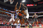 Pittsburgh guard Au'Diese Toney, left, and forward Eric Hamilton, right, trap Louisville forward Dwayne Sutton (24) along the baseline during the second half of an NCAA college basketball game in Louisville, Ky., Friday, Dec. 6, 2019. Louisville won 64-46. (AP Photo/Timothy D. Easley)