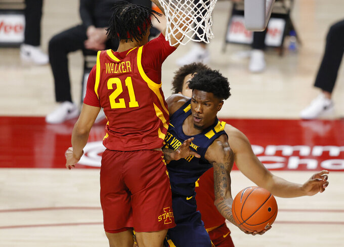 West Virginia guard Kedrian Johnson looks to pass under the basket around Iowa State guard Jaden Walker, left, during the first half of an NCAA college basketball game, Tuesday, Feb. 2, 2021, in Ames, Iowa. (AP Photo/Matthew Putney)