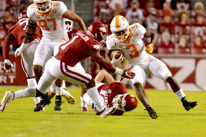Tennessee running back Eric Gray (3) is tackled by Arkansas defensive back Jalen Catalon (1) during the first half of an NCAA college football game Saturday, Nov. 7, 2020, in Fayetteville, Ark. (AP Photo/Michael Woods)