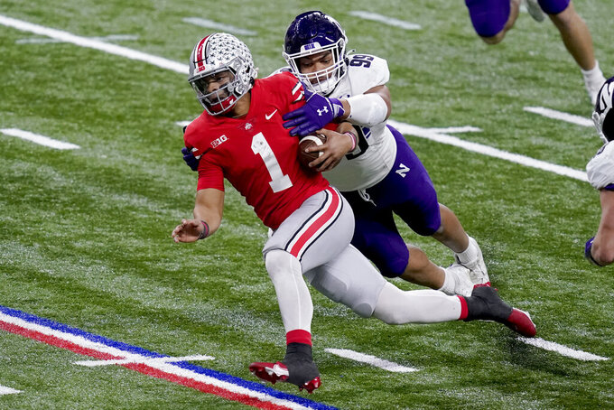 Ohio State quarterback Justin Fields (1) is pulled down by Northwestern defensive end Earnest Brown IV (99) during the second half of the Big Ten championship NCAA college football game, Saturday, Dec. 19, 2020, in Indianapolis. (AP Photo/Darron Cummings)