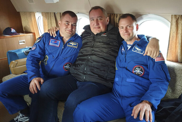 In this photo made available by Roscosmos on Friday, Oct. 12. 2018, agency leader Dmitry Rogozin, center, embraces cosmonaut Alexei Ovchinin, left, and U.S. astronaut Nick Hague at Star City, Russia, a space training center outside Moscow. After an aborted launch on Thursday, Rogozin promised that Hague and Ovchinin will be given another chance soon to work on the International Space Station. (Roscosmos via AP)