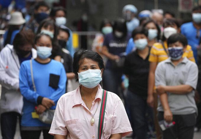 Local residents line up, waiting for the coronavirus testing at a market in Bangkok, Thailand, Friday, June 11, 2021. (AP Photo/Sakchai Lalit)