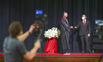 McCracken County High School Principal Matthew Houser, right, presents a diploma to 2020 graduate Ethan Bellamy, 18, of Paducah on Wednesday afternoon, May 20, 2020, during a live stream of the MCHS graduation as it's filmed by Shanden Simmons of Socially Present in the school's auditorium in Paducah, Ky. (Thomas Dean Stewart/The Paducah Sun via AP)