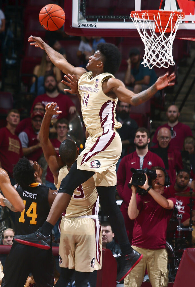 Florida State guard Terance Mann (14) leaps to reject a shot by Winthrop guard Adam Pickett (14) during the second half of an NCAA college basketball game in Tallahassee, Fla., Tuesday, Jan. 1, 2019. Florida State won 87-76. (AP Photo/Phil Sears)