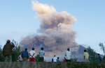 FILE- In this Jan. 24, 2018, file photo, residents watch as Mayon volcano erupts anew as seen from Legazpi city, Albay province, around 340 kilometers (200 miles) southeast of Manila, Philippines. (AP Photo/Bullit Marquez, File)