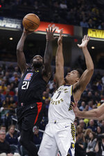 Los Angeles Clippers' Patrick Beverley (21) shoots over Indiana Pacers' Malcolm Brogdon (7) during the first half of an NBA basketball game, Monday, Dec. 9, 2019, in Indianapolis. (AP Photo/Darron Cummings)