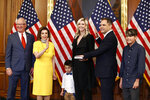 House Speaker Nancy Pelosi of Calif., second from left, conducts a ceremonial swearing-in for Rep. Mike Garcia, R-Calif., second from right, joined by his wife Rebecca and sons Jett, center, and Preston, on Capitol Hill in Washington, Tuesday, May 19, 2020. Standing alongside Pelosi is former Rep. Buck McKeon, R-Calif. (AP Photo/Patrick Semansky)
