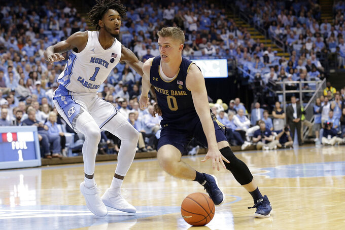 North Carolina guard Leaky Black (1) guards Notre Dame guard Rex Pflueger (0) during the second half of an NCAA college basketball game in Chapel Hill, N.C., Wednesday, Nov. 6, 2019. North Carolina won 76-65. (AP Photo/Gerry Broome)