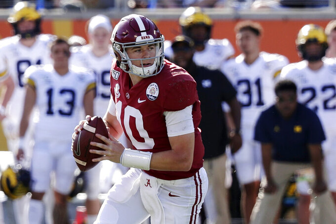 FILE - In this Jan. 1, 2020, file photo, Alabama quarterback Mac Jones (10) rolls ut as he looks for a receiver during the first half of the Citrus Bowl NCAA college football game against Michigan in Orlando, Fla.  No. 2 Alabama doesn't look like a team that lost quarterback Tua Tagovailoa and two first-round receivers. Mac Jones still has a selection of some of the SEC's best playmakers, including Jaylen Waddle. (AP Photo/John Raoux, File)