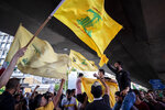 Hezbollah and Amal supporters wave Hezbollah and Iranian flags as they shout slogans against Israel and U.S. during a protest in the southern suburb of Beirut, Lebanon, Sunday, June 28, 2020. The protest came hours after Lebanon's foreign minister summoned the U.S. ambassador to Beirut over comments, she made recently in which she criticized Hezbollah. The meeting between Foreign Minister Nassif Hitti and Ambassador Dorothy Shea is scheduled for Monday afternoon. (AP Photo/Hassan Ammar)