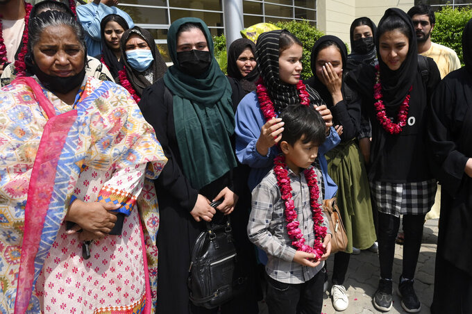 Members of Afghanistan's women soccer team and their families pose for a photograph after they were greeted by officials of the Pakistan Football Federation, in Lahore, Pakistan, Wednesday, Sept. 15, 2021.  Officials and local media said Wednesday that an unspecified number of Afghan women players and their family members were allowed to enter in Pakistan after apparently fleeing their country for security reasons. (AP Photo/Waleed Ahmed)