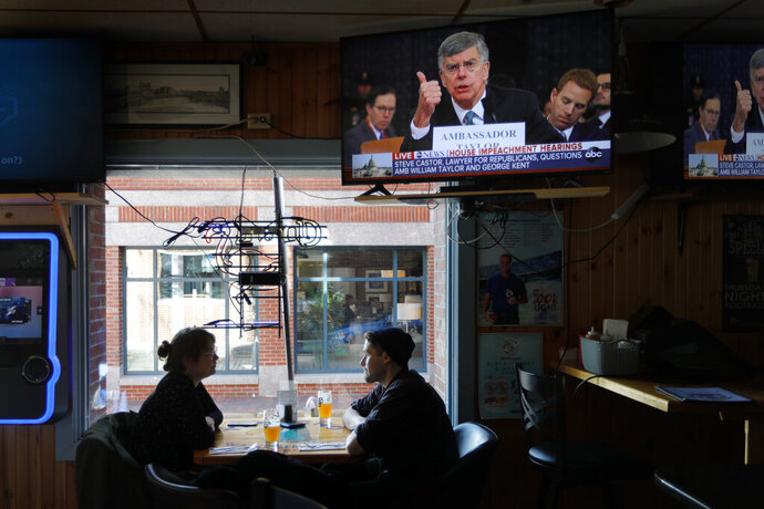Olivia Tobin and her fiancé, Jordan Ashby, ignore the televised impeachment hearings playing on monitors at the Commercial Street Pub, Wednesday, Nov. 13, 2019, in Portland, Maine. Tobin is an Irish citizen who has a green card to live and work in the U.S. and said she only pays attention to the hearings if it seems likely that the Trump will be held accountable. (AP Photo/Robert F. Bukaty)
