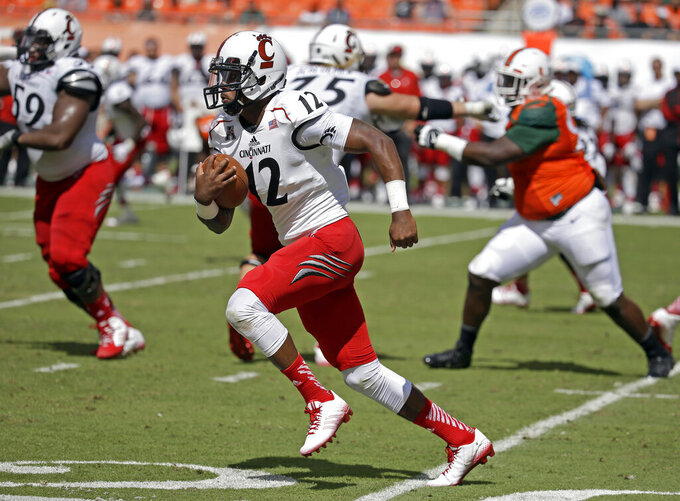 FILE - In this Oct. 11, 2014 file photo, Cincinnati quarterback Jarred Evans (12) runs in the second half of an NCAA college football game against Miami in Miami Gardens, Fla. Evans, one 195 Americans who were flown out of the city of Wuhan Wednesday on a plane chartered by the U.S. government, says he's wearing a mask and gloves and taking special precautions while staying at March Air Reserve Base in Riverside, Calif. (AP Photo/Lynne Sladky, File)