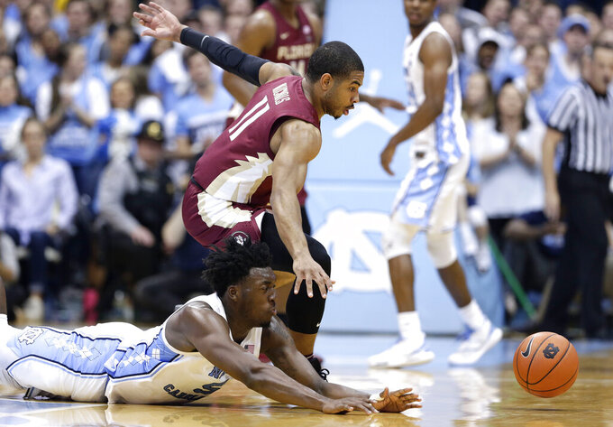 North Carolina's Nassir Little, bottom, dives while chasing the ball with Florida State's David Nichols (11) during the second half of an NCAA college basketball game in Chapel Hill, N.C., Saturday, Feb. 23, 2019. (AP Photo/Gerry Broome)