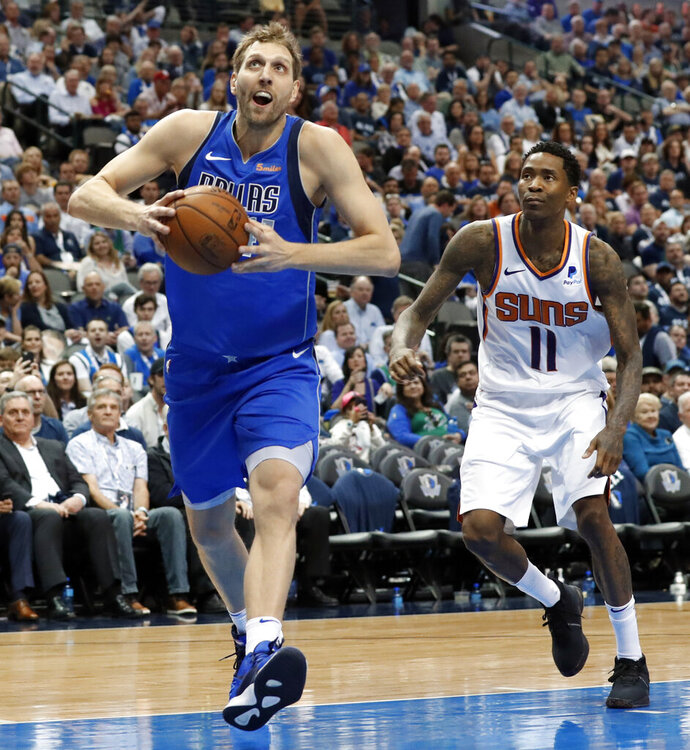 Dallas Mavericks forward Dirk Nowitzki (41) drives past Phoenix Suns guard Jamal Crawford (11) to the basket for a dunk during the second half of an NBA basketball game in Dallas, Tuesday, April 9, 2019. (AP Photo/Tony Gutierrez)