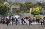 Demonstrators clash with the police during a protest to demand the resignation of President Juan Orlando Hernandez, in Tegucigalpa, Honduras , Thursday, Oct. 24 2019. Calls for President Hernandez's resignation came after his younger brother was convicted on drug trafficking charges in New York and testimony implicated the president in his drug enterprise. (AP Photo/Elmer Martinez)