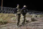 Police officers guard an entrance to the Nevada Test and Training Range near Area 51 Friday, Sept. 20, 2019, near Rachel, Nev. People gathered at the gate inspired by the