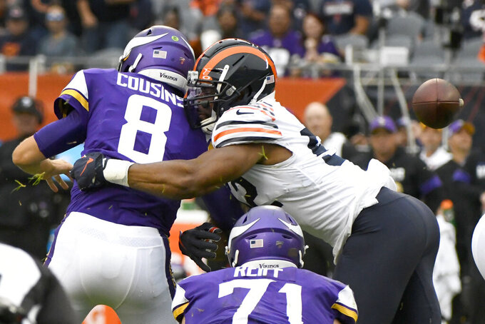 Minnesota Vikings quarterback Kirk Cousins (8) fumbles the ball as he is sacked for a 7-yard loss by Chicago Bears outside linebacker Khalil Mack, right, during the second half of an NFL football game Sunday, Sept. 29, 2019, in Chicago. The Bears recovered the fumble. (AP Photo/Matt Marton)