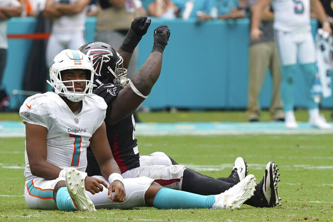 Miami Dolphins quarterback Tua Tagovailoa (1) and Atlanta Falcons defensive tackle Grady Jarrett (97) react after a pass thrown by Tagovailoa was intercepted, during the second half of an NFL football game, Sunday, Oct. 24, 2021, in Miami Gardens, Fla. (AP Photo/Hans Deryk)