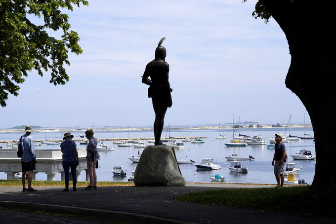 Visitors stand near a 1921 statue of the Wampanoag leader Massasoit, center, Wednesday, June 9, 2021, on Cole's Hill, in Plymouth, Mass. (AP Photo/Steven Senne)