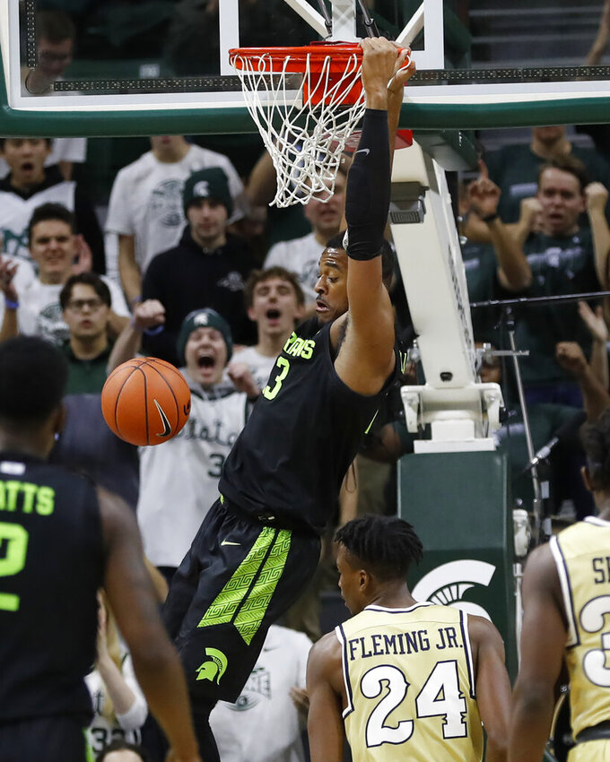 Michigan State forward Xavier Tillman, center, dunks during the first half of an NCAA college basketball game against Charleston Southern, Monday, Nov. 18, 2019, in East Lansing, Mich. (AP Photo/Carlos Osorio)