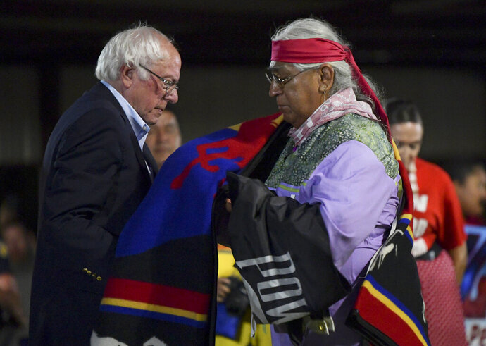 Democratic presidential candidate U.S. Sen. Bernie Sanders receives an honor blanket from Cornel Pewewardy at the annual Comanche Nation Fair Powwow, Sunday, Sept. 22, 2019, in Lawton, Okla. (AP Photo/Gerardo Bello)