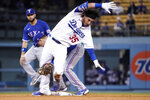 Los Angeles Dodgers' Cody Bellinger, right, is tagged out at second by Texas Rangers second baseman Nick Solak after trying to stretch a single into a double during the fourth inning of a baseball game Friday, June 11, 2021, in Los Angeles. (AP Photo/Mark J. Terrill)