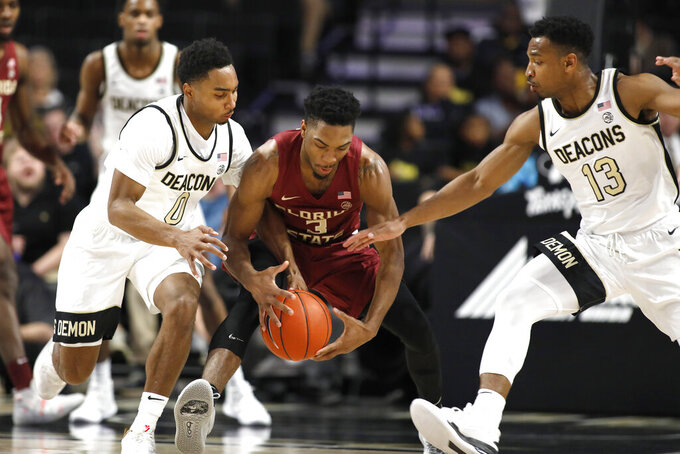 Florida State's Trent Forrest (3) reaches for the loose ball from Wake Forest's Brandon Childress (0) and Andrien White (13) in the first half of an NCAA college basketball game Wednesday, Jan. 8, 2020 in Winston-Salem, N.C. (AP Photo/Lynn Hey)