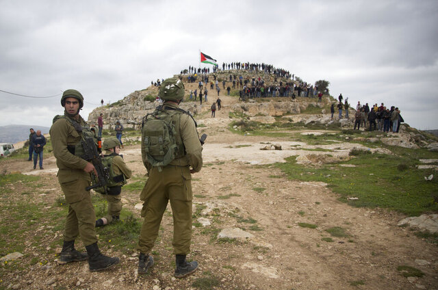 FILE - In this Monday, March 2, 2020 file photo, Israeli soldiers take position as Palestinian demonstrators gather during a protest against expansion of Israeli settlements, in the West Bank village of Beita near Nablus. Now that Prime Minister Benjamin Netanyahu has secured a new term in office, there's little to prevent him from annexing large parts of the West Bank as early as this summer. Netanyahu has broad support in the new parliament and a friendly ally in the White House for his long-promised goal. Annexation, the likely death blow to faded Palestinian hopes for independence, will be high on the agenda of U.S. secretary of state Mike Pompeo's blitz visit to Jerusalem next week. (AP Photo/Majdi Mohammed, File)